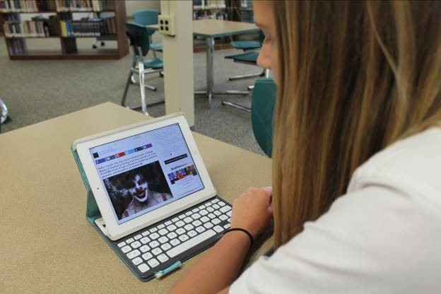 Sophomore+Emily+Susitko+reads+a+BuzzFeed+article+about+the+clowns+sightings+to+stay+informed+about+the+issue.+%28Photo+Credit%3A+Sydney+Hughes%29