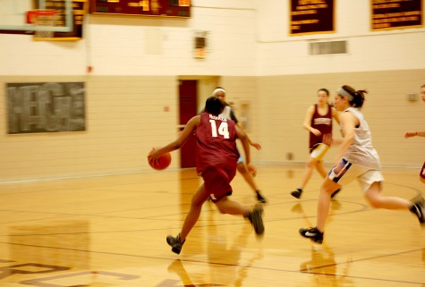 Senior Janelle McQueen dribbles down the court to take a shot.