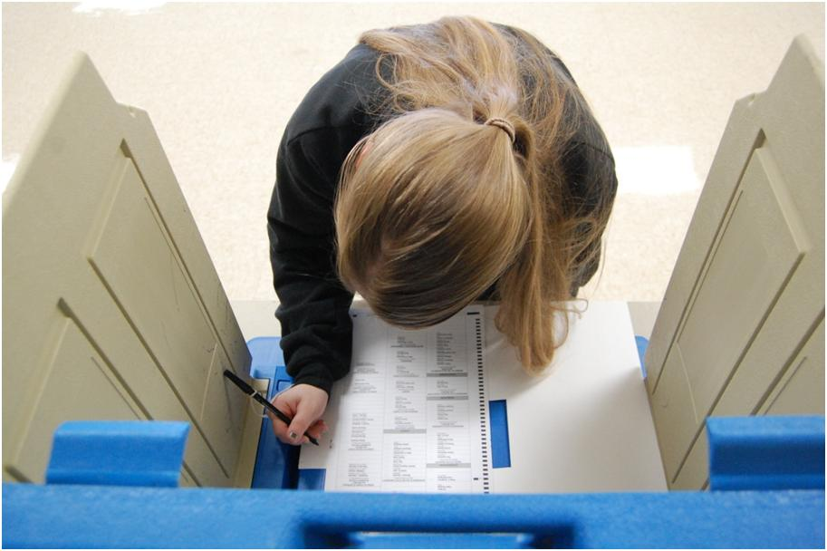 Senior Anna Larson prepares to vote in a real voting booth, set up in the school lobby.