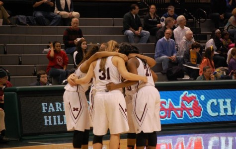 Some Mercy varsity basketball players huddle together during a timeout at The Breslin Center. The ladies fell in the State Semifinal to rival Marian, 67 to 55.