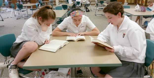 Heather Lillystone, Jenna Cham, and Julia Kirby (from the left) are immersed in reading The Kite Runner by Khaled Hosseini: the first book the club is reading before the STARS next meeting commences on Oct. 31 (Photo Credit: Ihechi Ezuruonye).