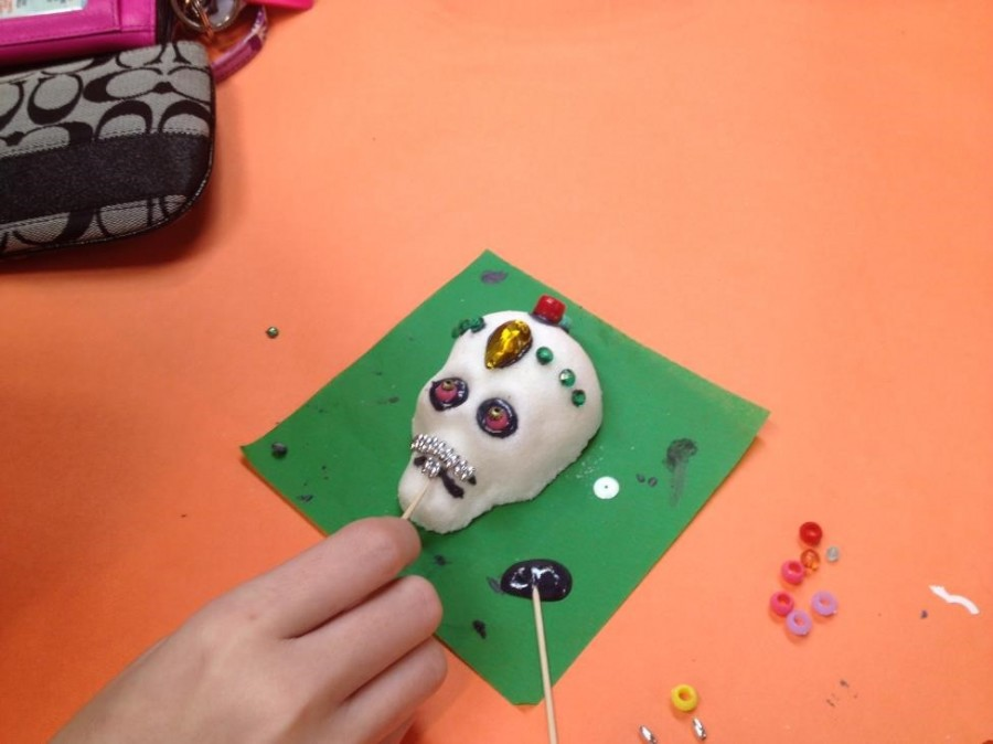 Students used colored frosting and sequins to decorate their sugar skulls (Photo Credit: Theresa Benton).