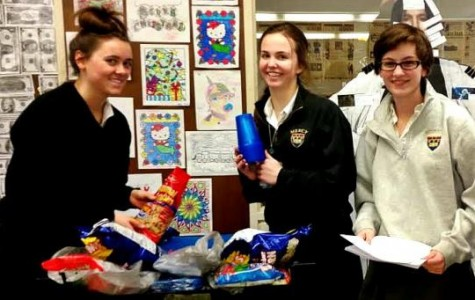JCL board members Jensen Pecora (left), Molly Murphy (middle) and Phil Engel (right) prepare the festive snacks JCL members get to eat in addition to watching a movie and playing bingo (Photo credit: Ihechi Ezuruonye).