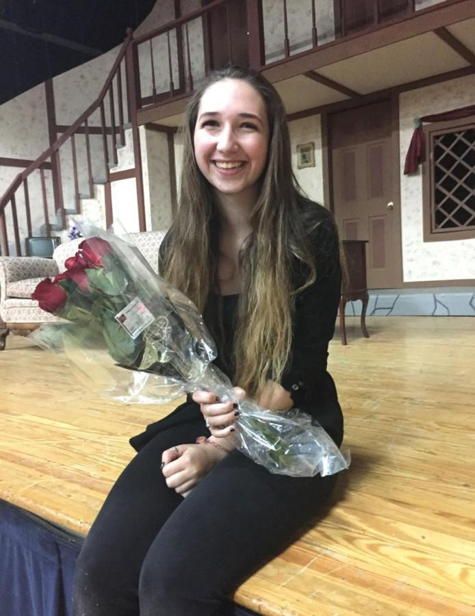Junior+Summit+Dempster+sits+in+front+of+the+set+of+%22Noises+Off%21%22+with+roses+and+a+big+smile+after+a+successful+opening+night.+%28Photo+credit%3A+Caitlin+Somerville%29