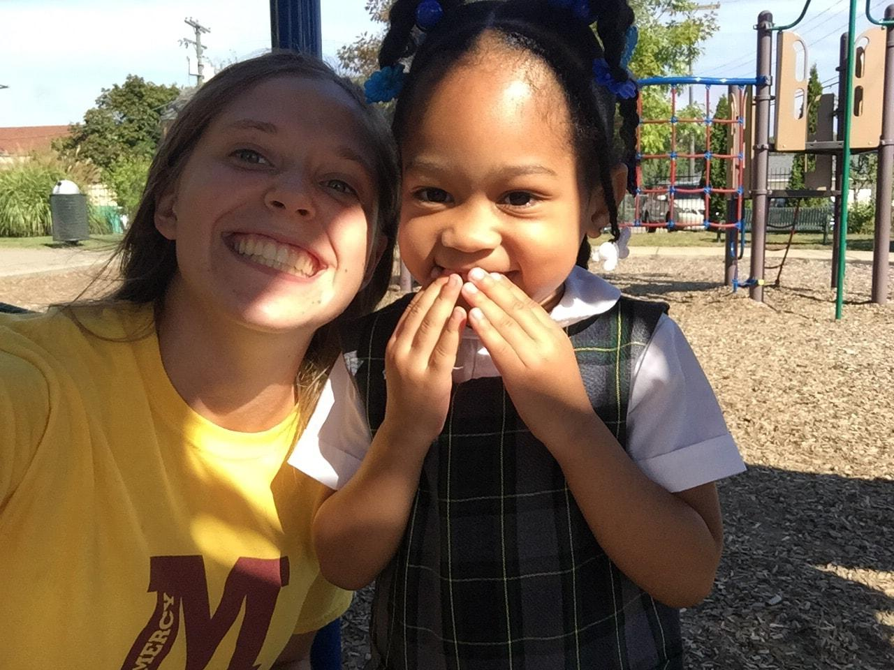 Gesu student Arianna (right) poses with Mercy senior Allia McDowell, hiding her smile from the camera after a long day of playing. (Photo credit: Allia McDowell)
