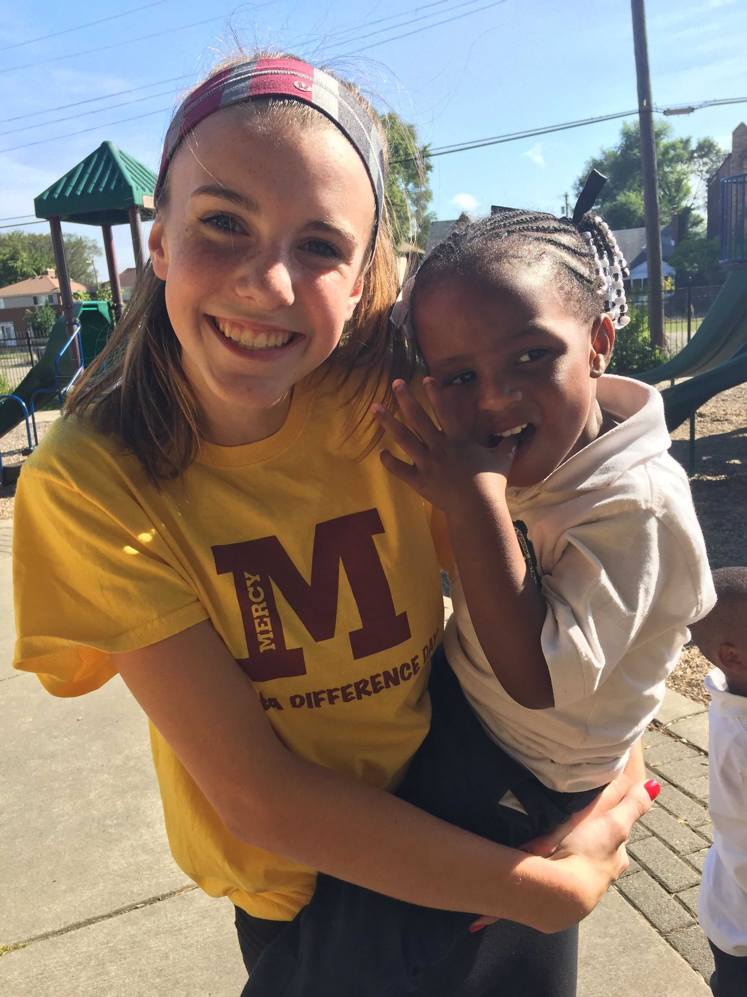 Mercy sophomore Maggie Belevie holds the Gesu student she spent her day with. According to Delevie, she and the young girl played tag and climbed the jungle gym. (Photo credit: Allia McDowell)