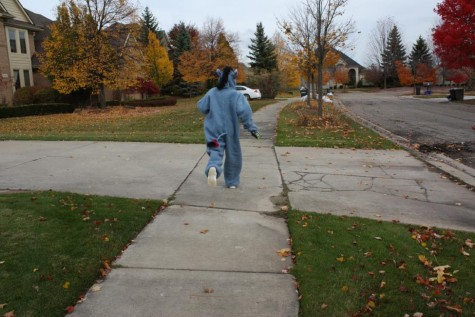 Freshman Emily Susitko is running to the next house in her trick or treating expedition, eager to see what treats await her. (Photo credit: Sydney Hughes)