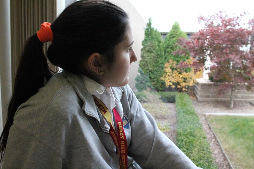 Senior Natalie Cieslak looks longingly out into the gloomy fall sky, wishing there was sun. Cieslak, like many others, feels the effects of mild depression during the winter months. (Photo illustration: Simone Rhodes)