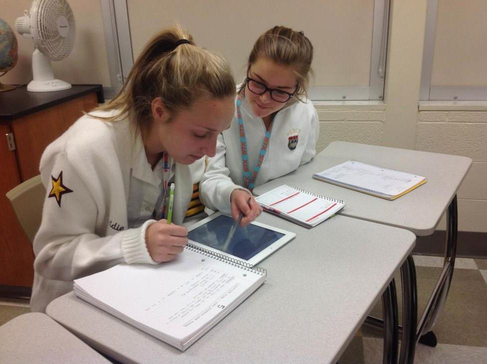Erin Gormley performs a small act of kindness by helping Maddie Erdman prepare for her upcoming physics test. (Photo credit: Bridgette Conniff)
