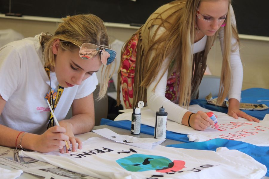 """Each French I, II, and III student decorated a t-shirt with the words """"Tout Va Bien Avec le Français"""" and """"La Semaine Nationale du Français"""" as well as their own creative design. Here, juniors Olivia Makela and Mary Doman design their shirts. (Photo Credit: Anastasia Warner)"""