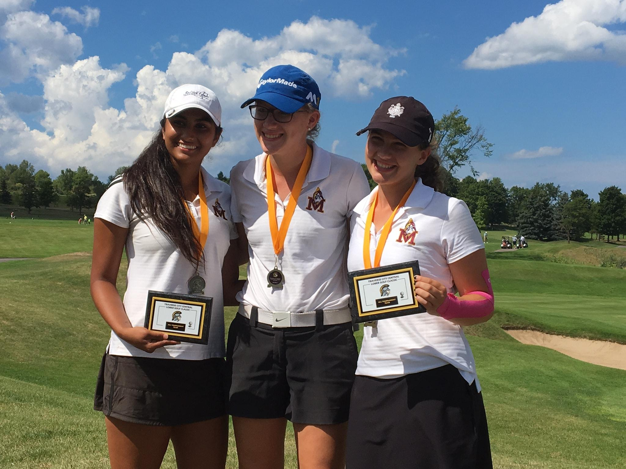 Sophomore Mia Sooch (left) smiles with her victory medal and plaque for making the All-Tournament team for the Traverse City Central Lober Golf Classic, next to senior Marissa Lobbia (middle), and sophomore Sophie Vanderwheele (right). Photo Credit: Mia Sooch