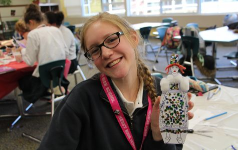 Sophomore Nathalie Gijsbers shows off the santon she created during the meeting. (Photo Credit: Karina Lloyd)