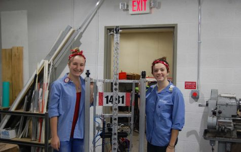 Team members senior Elise Scarchilli and junior Mary Marquette stand next to their award winning robot in the team's new building site. (Photo Credit: Isha Ganguli)