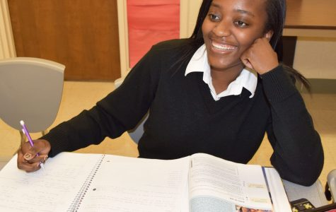 Senior Chiaka Ibe smiles as she works during her off time to complete homework. Ibe is determined to make her final semester at Mercy High School one to remember. (Photo Credit: Molly Lyons)