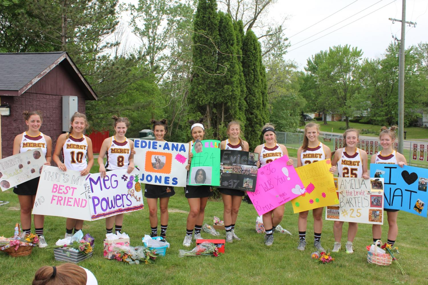 Mercy Varsity Lacrosse seniors hold up the posters their fellow teammates have given them on senior night. (From right to left: Ciara Lopus, Emma Easson, Meg Powers, Edie Jones, Ellie Gouvia , Evie Drukker, Maria Bowen, Hannah Roegner, Amelia Bartels, Natalie Masopust) (Photo courtesy of: Amelia Bartels)