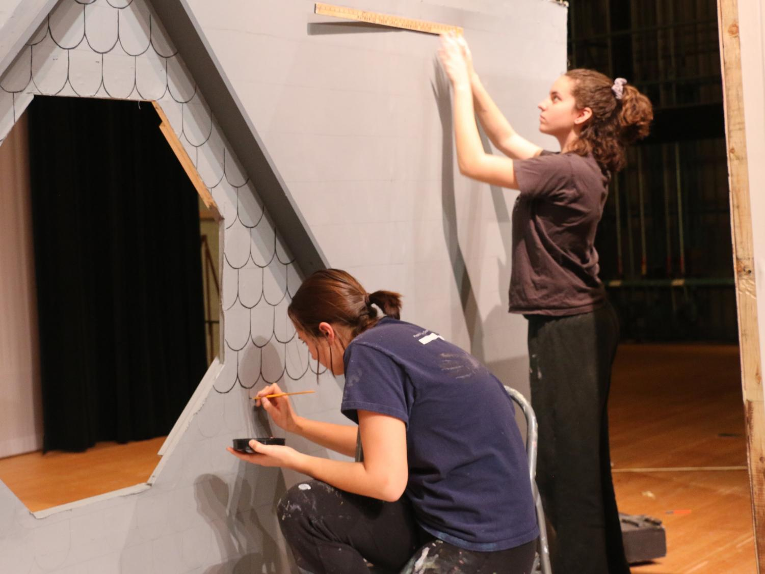 Senior Abbey Hembree paints individuals shingles on the rooftop while other members of Stage Crew build and paint other parts of the set.