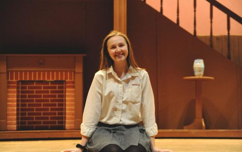 Cara Forfinski sits on the edge of the Mercy stage, awaiting rehearsal for her last Mercy musical, Mary Poppins.