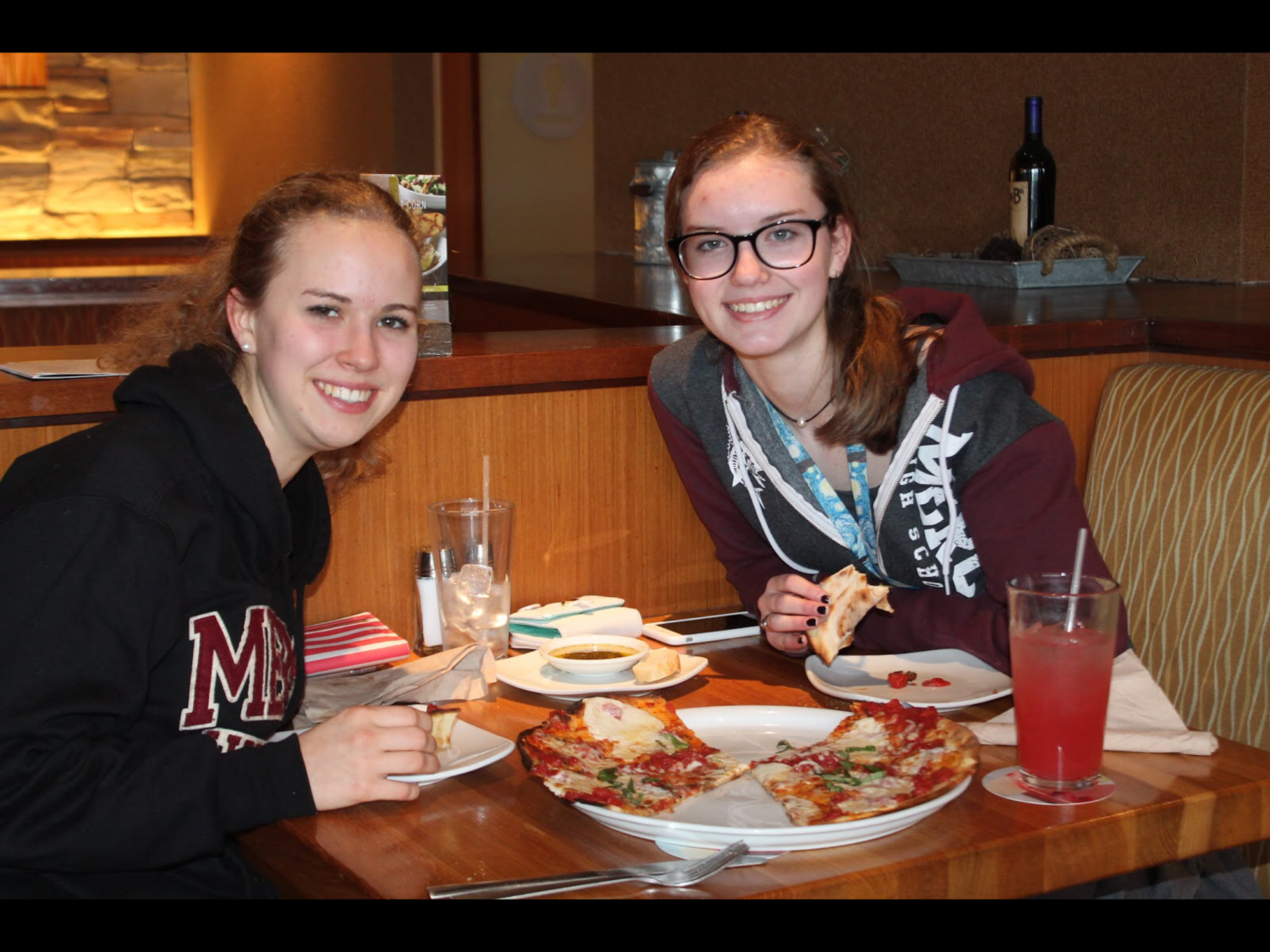Seniors Kathryn Wolf (left) and Mackenzie Farrow split a margherita pizza, a CPK classic, while supporting Mercy through spirit wear and their bill.