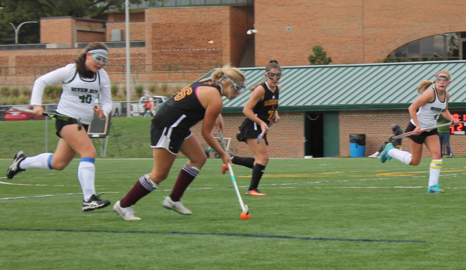 Senior Sarah Cassidy dribbles past the defense in one of her last field hockey games at Mercy. Photo by Keiley Black