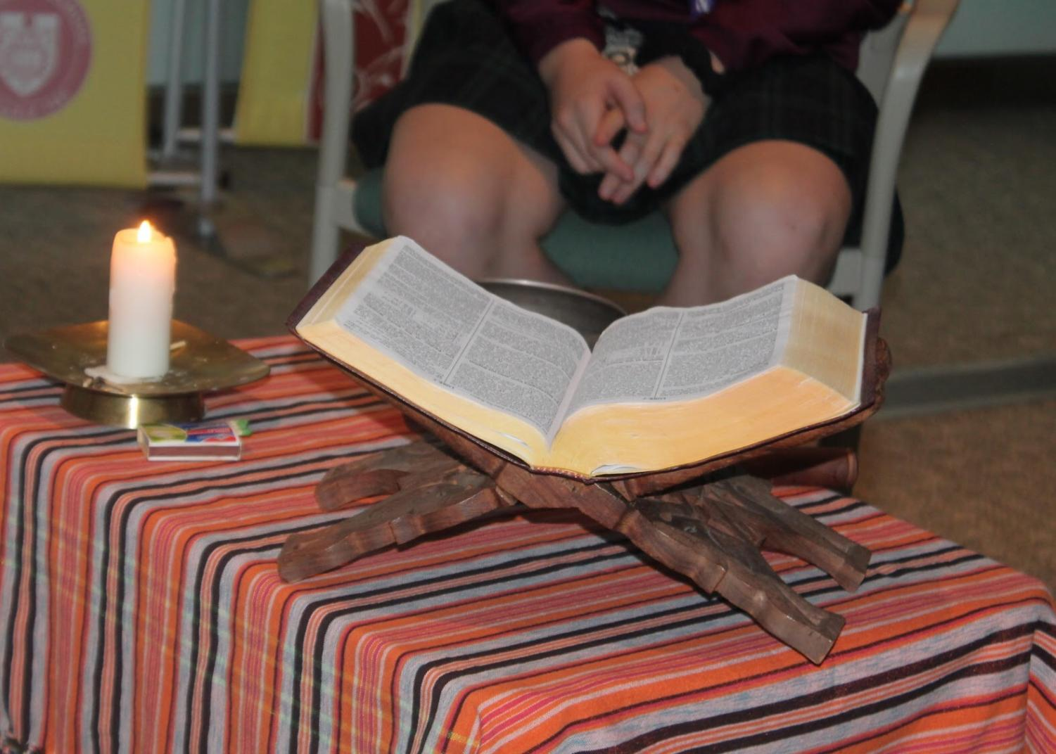 The bible and candle centred in the circle of chairs. The candle is lit in the beginning of prayer and the bible often gets passed around if students would like to read.  Photo by Hailey Kallabat