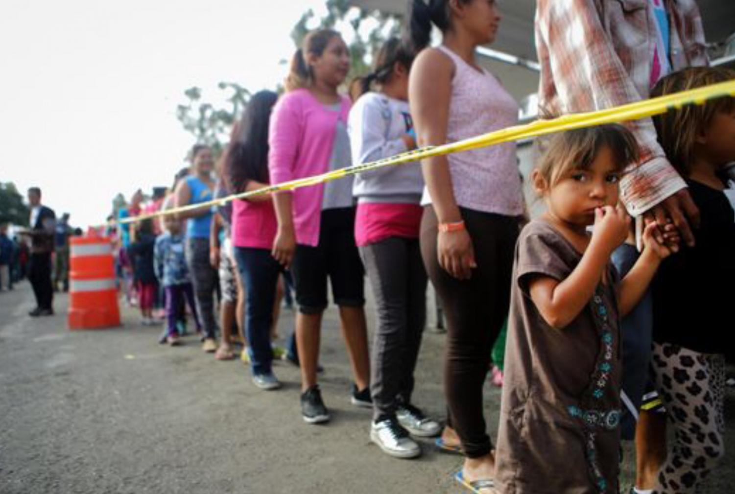 Hundreds of migrants and their families line up to receive breakfast during their stay at a temporary shelter in Tijuana, Mexico.  Fair use: Mario Tama/Getty Images