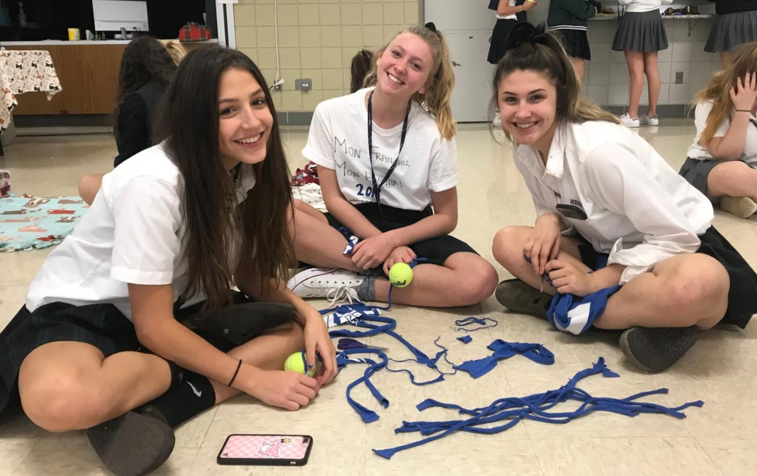 Sophomores Sofia Genrich, Caroline Wiseley, and Ashley Phillips work on making toys for shelter dogs during their most recent club meeting.  Photo used with permission from Eli Lyons
