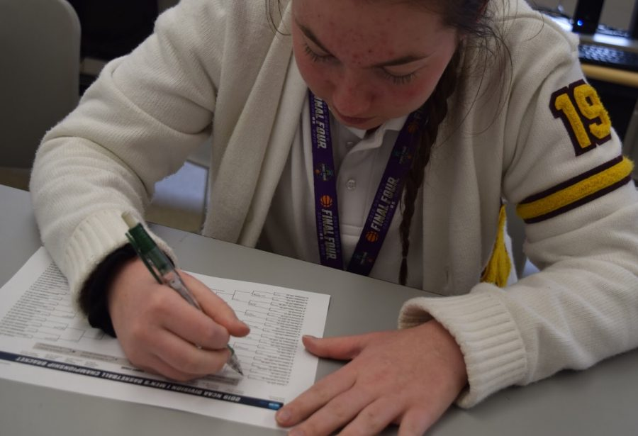 Senior Annie Treharne works on her March Madness bracket, carefully selecting the teams she thinks will be most successful.  Photo by Colleen Thomson