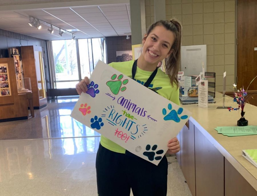 """Junior Genevieve Sale, a member of Mercy's Animal Rights Club, takes a stand against animal cruelty with this sign reading """"Animals Have Rights, Too!""""  Photo by: Mary McGreevy"""