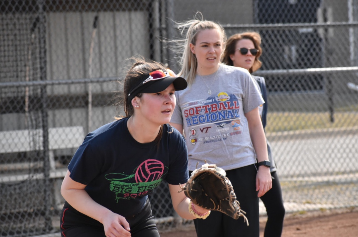 Junior Emma Dompierre (left) prepares to catch a ball coming her way while her new coach, Kayce Nieto (middle), observes. Photo by Caitlin Flynn