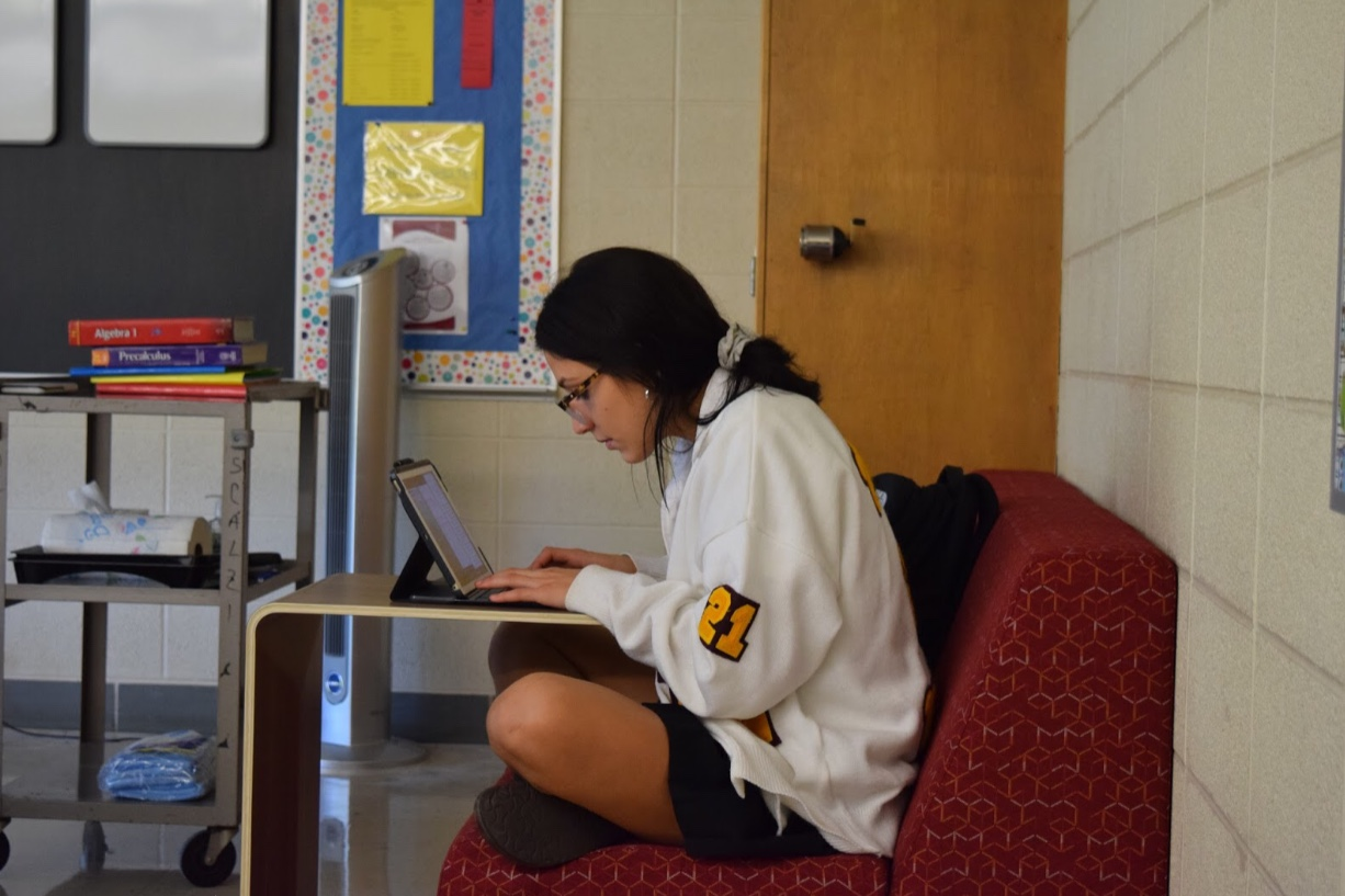 Junior Sofia Genrich takes notes on a new couch in her Algebra II class in room N-4. Photo by Megan Mallie