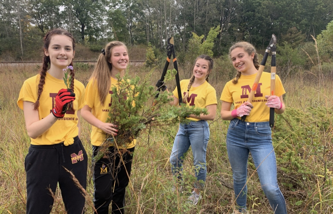 Students help cut down harmful plants to help maintain the St. Joes' Ann Arbor prairie during their Mercy Make a Difference Day trip. Photo by Caitlin Flynn