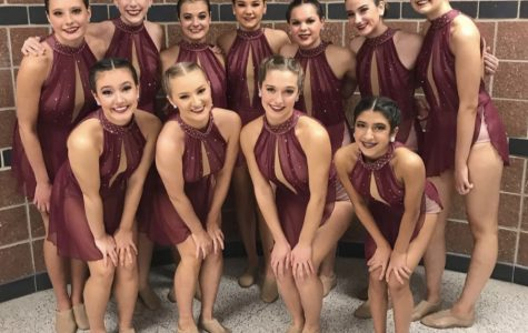 The Mercy Varsity dance team poses in their costumes as they prepare to compete. Photo used with permission from Brittany Burns