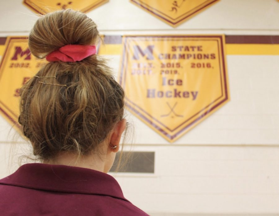 Mercy senior and captain of the Mercy Varsity Ice Hockey Team (MVH) Sydney Takla looks at the hockey state championship banner strung high in the gym as she reflects on her past years playing for the Marlins. Photo by Carrie Jefferson