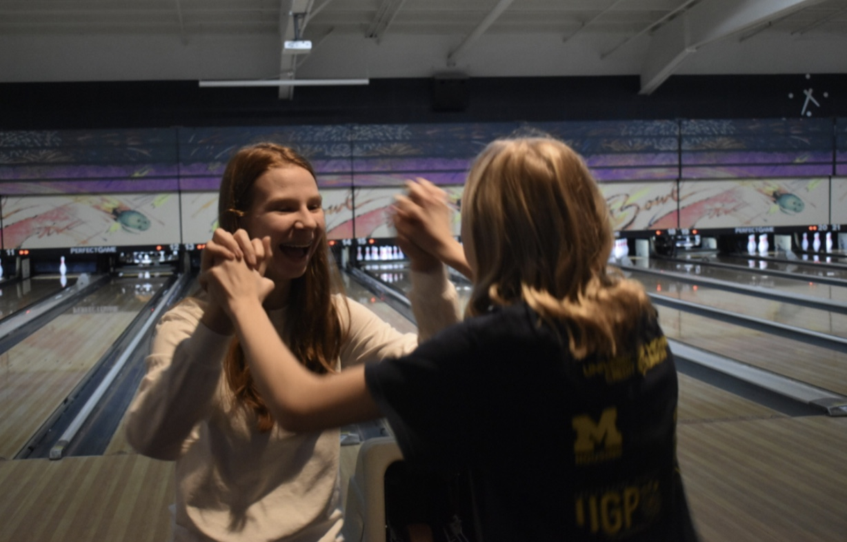 Mercy's Varsity bowling players laugh together during one of their practices while waiting for their next turn. Photo by Caitlin Flynn