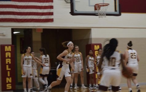 Freshman Maya White moves into position while practicing free throws during halftime. Photo by Megan Mallie