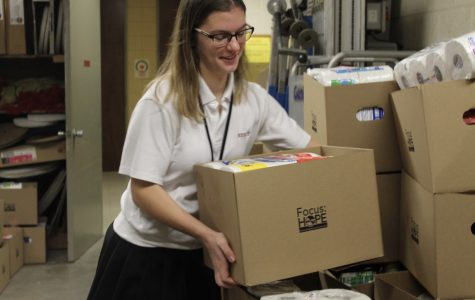 Junior Jules Saval places a box down for the Focus Hope food drive so that they can load the semi truck to reach their goal. Photo by Dunya Kizy