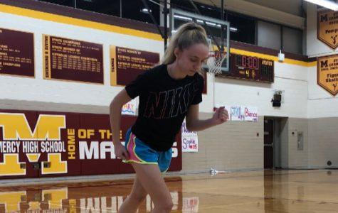 Junior Mackenzie Sullivan takes a jog around the gym to warm up for practice. Photo by Maddie Sullivan