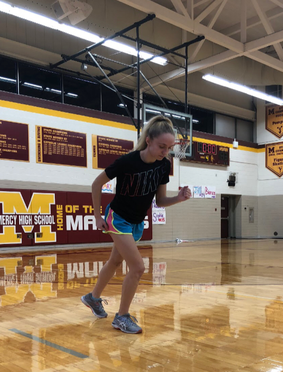 Junior Mackenzie Sullivan takes a jog around the gym to warm up for practice. Photo by Maddie Sullivan