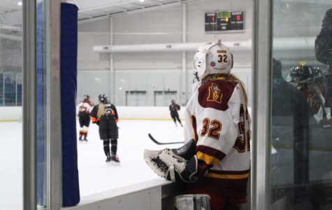 Senior goalie Charlotte Syke watches from the bench as her teammates compete against Northville High School on Friday, February 28th. Photo by Julia Canty