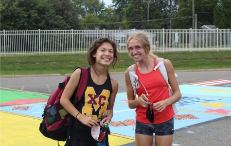 Seniors Katie Kim and Mackenzie Sullivan head to practice while carrying their personal running equipment and masks.